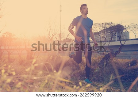 Handsome male athlete running in the park at sunset (little motion blur, intentional sun glare and vintage color) - stock photo