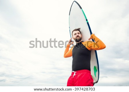 Handsome male bearded surfer on the beach holding a surf board and watching the waves in Kuta, Bali