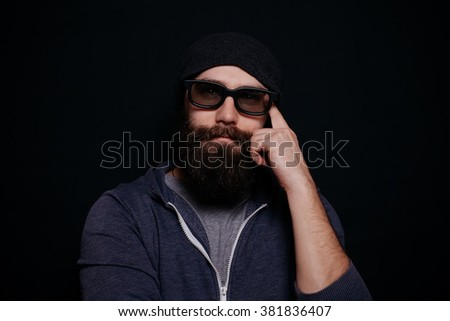 Handsome male big beard in glasses and hat, studio shot on black background, hand near Temple