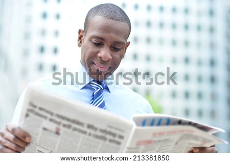 Handsome male business executive reading a newspaper - stock photo