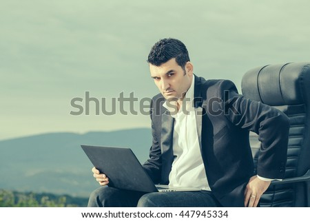 handsome male businessman with courageous face in black formal jacket and white shirt working on laptop sitting on leather office arm chair outdoor on cloudy sky background