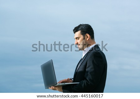 handsome male businessman with serious face in black formal jacket and white shirt working on laptop outdoor on cloudy sky background