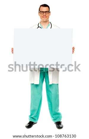 Handsome male doctor displaying white advertising board, full length shot - stock photo