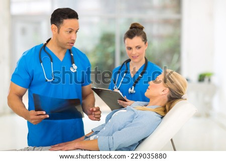 handsome male doctor talking to senior patient before examining - stock photo