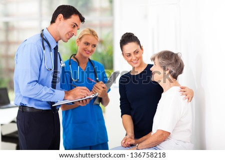 handsome male doctor writing medical prescription for senior patient - stock photo