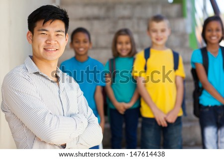 handsome male elementary educator with students on background - stock photo
