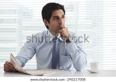 Handsome male executive in deep thought with newspaper at office - stock photo