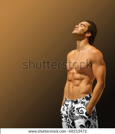 Handsome male fitness model shirtless with hands in pockets looking up with lots of copy space - stock photo