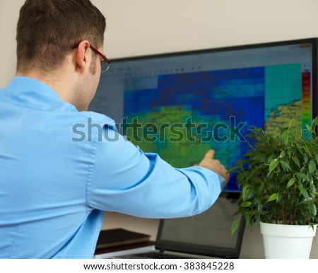 Handsome male meteorologist working with touchscreen. - stock photo