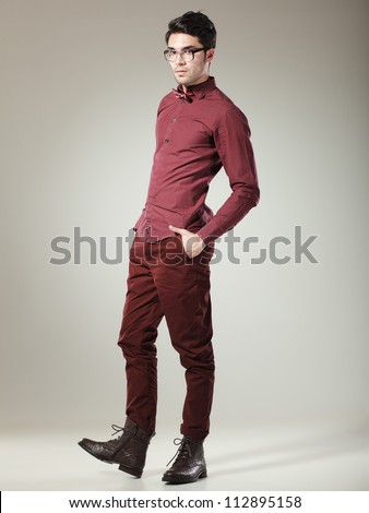 handsome male model dressed elegant posing in the studio looking serious - stock photo