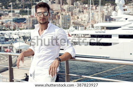 Handsome male model posing in front of a luxury yacht during summer vacation
