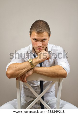 Handsome male model sitting on the chair. - stock photo