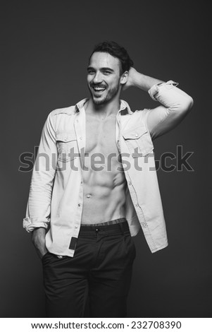 handsome male model with muscle standing unbuttoned and smiling, black and white