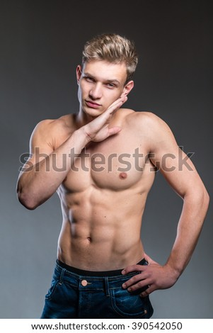 Handsome male model with muscular body posing in studio  - stock photo