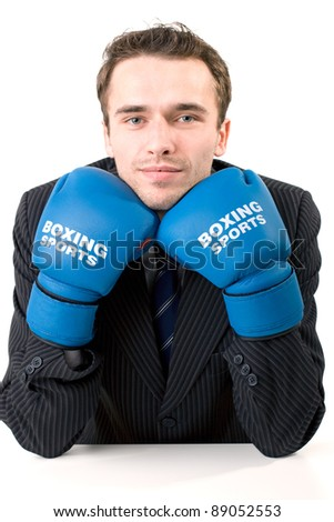 Handsome male model, young man, attractive businessman in suit and gloves sitting in office ready to box, made in studio on white background - stock photo