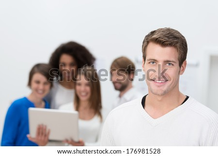Handsome male office worker with team in the background - stock photo