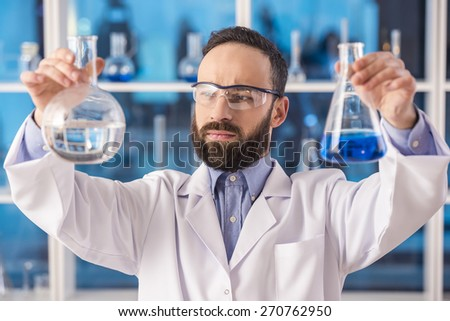 Handsome male scientist researcher in safety glasses observing liquid in flasks in a laboratory. - stock photo