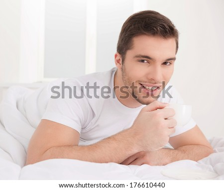 handsome male smiling laying in bed. Attractive young man wearing pyjama - stock photo
