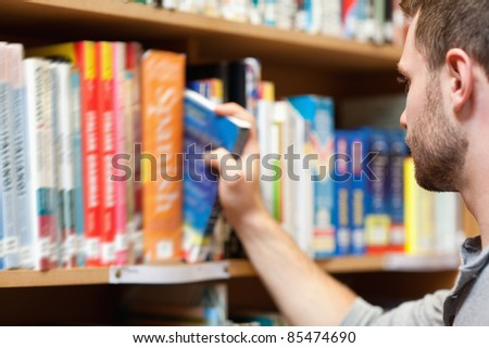 Handsome male student picking a book in a library