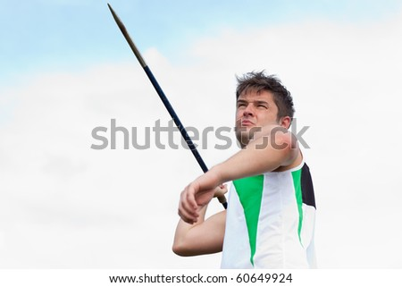 handsome male throwing a javelin outdoors - stock photo