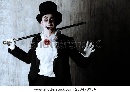 Handsome male vampire in a tail-coat and top-hat. Halloween. Dracula costume. - stock photo