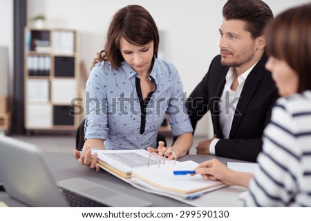 Handsome Man Admiring his Pretty Wife While Discussing the Contract with the Real Estate Agent Inside the Office. - stock photo