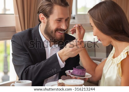 Handsome man and beautiful woman are sitting at the table in cafe. They are feeding each other with cake and smiling. They are looking at each other with love - stock photo