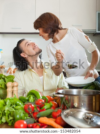 Handsome man and beautiful woman with vegetables in the kitchen of his home