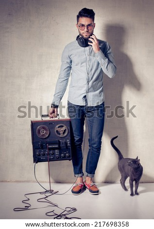 handsome man and cat listening to music on a magnetophone against grunge wall - stock photo
