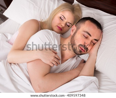 Handsome man and girlfriend hugging while sleeping together - stock photo