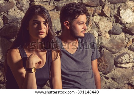 Handsome man and gorgeous woman posing outdoor with stone wall in background - stock photo