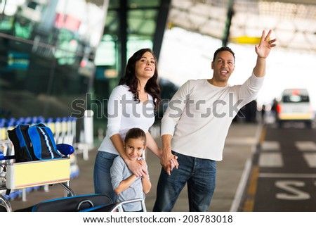 handsome man and his family hailing taxi at airport - stock photo