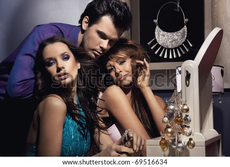 Handsome man and two elegant ladies preparing to a party - stock photo