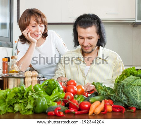 Handsome man and woman with vegetables in the kitchen of his home