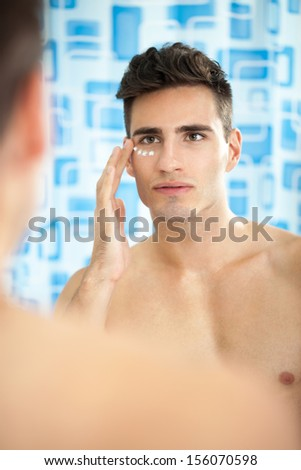 Handsome man applying cream on his face in bathroom  - stock photo
