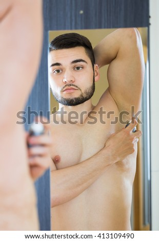 Handsome man applying deodorant at home - stock photo