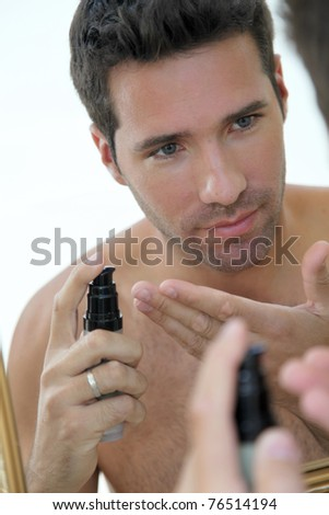 Handsome man applying moisturizer in front of mirror - stock photo