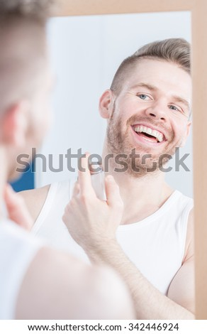 Handsome man applying perfume at the morning - stock photo