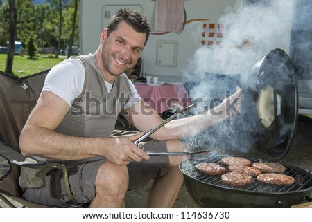 Handsome man at a barbecue grill with smoke