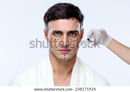 Handsome man at plastic surgery with syringe in his face - stock photo