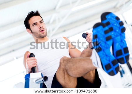Handsome man at the gym working out - stock photo