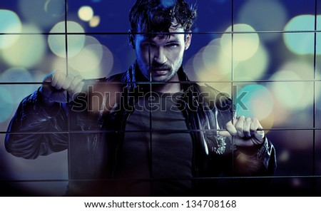 Handsome man behind the fence - stock photo