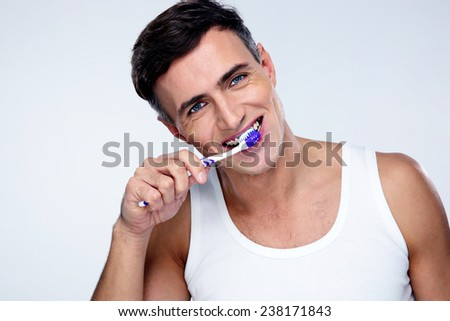 Handsome man brushing his teeth over gray background