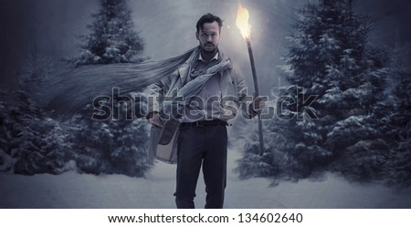 Handsome man carrying a burning torch - stock photo