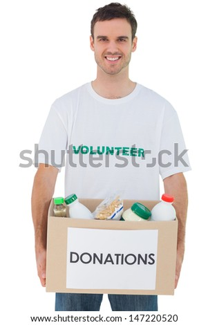 Handsome man carrying donation box with food on white background