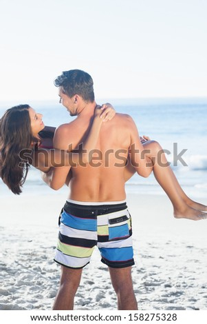 Handsome man carrying his girlfriend in his arms on the beach