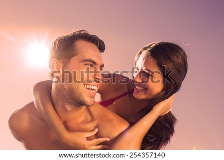 Handsome man carrying his girlfriend on his back on the beach - stock photo