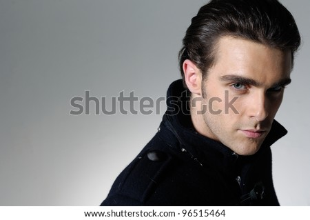 Handsome man casually leaning against in light background