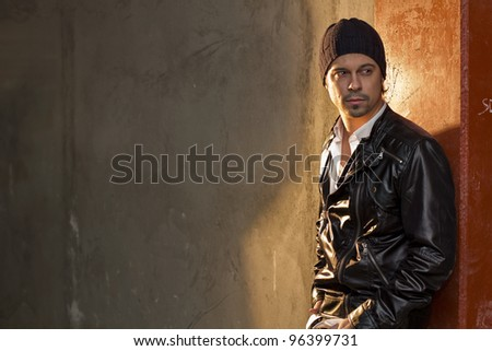 Handsome man casually leaning against the wall, relaxed and confident. - stock photo