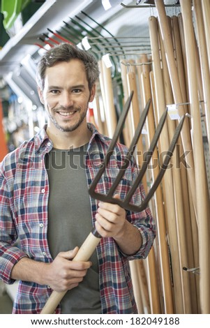 handsome man choosing a tool in a garden center